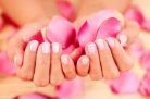 female hand with petal of rose - beauty treatment